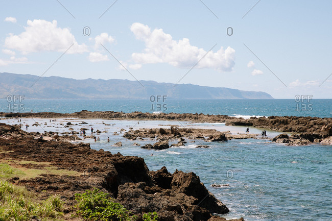 Tourists exploring waters in Shark's Cove on the North Shore of Honolulu, Oahu, Hawaii
