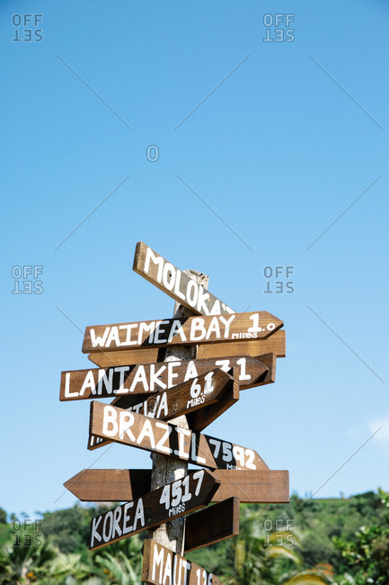 Directional sign with wooden arrows and distances to places near and far in Honolulu, Oahu, Hawaii