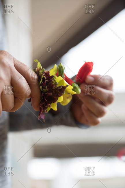 Person assembling a traditional lei with flowers close up