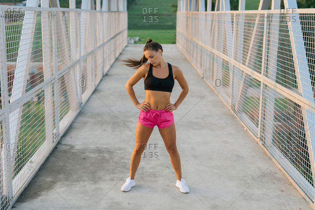 Young female runner warming up and stretching before jogging
