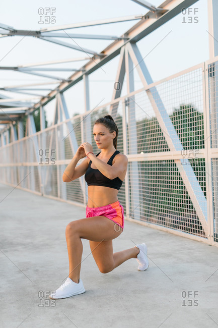 Young female runner warming up before workout and doing lunges on a bridge