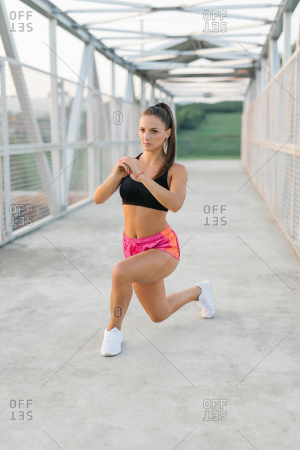 Athletic young female doing lunges while warming up before workout on a bridge