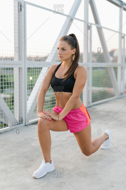 Side view of an athletic young female doing lunges while warming up before workout on a bridge
