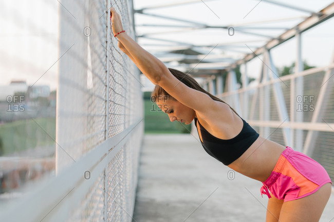 Side view of an athletic young female warming up before workout and stretching on a pedestrian bridge