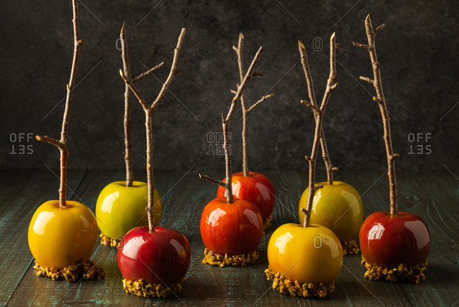 Caramel apples with branch sticks on rustic background