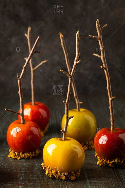 Green and red caramel apples with branch sticks on rustic background