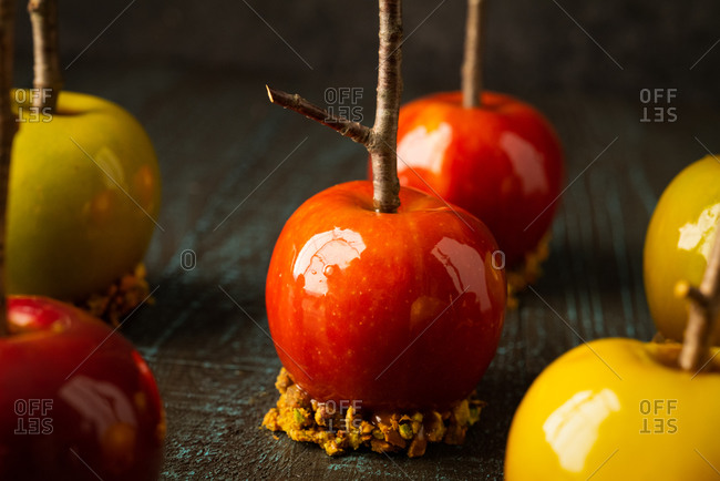 Close up of caramel apples with branch sticks on rustic background