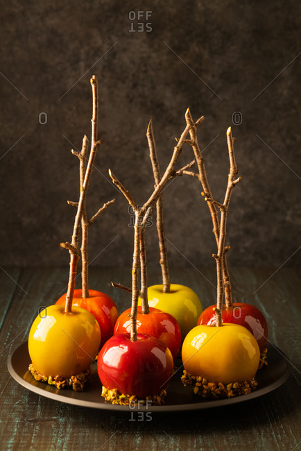 Caramel apples with branch sticks on a black plate