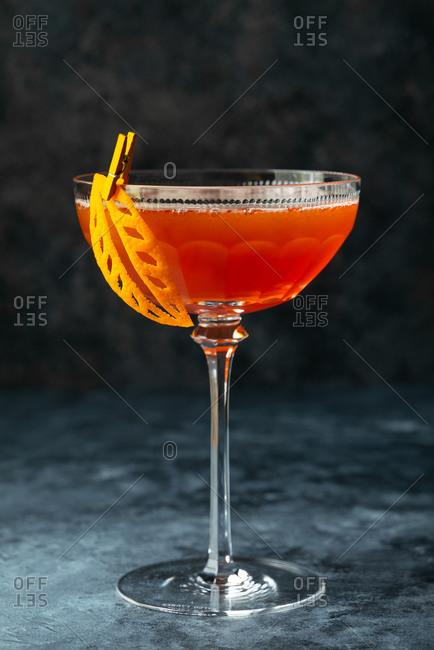 Fall cocktail with leaf orange peel garnish