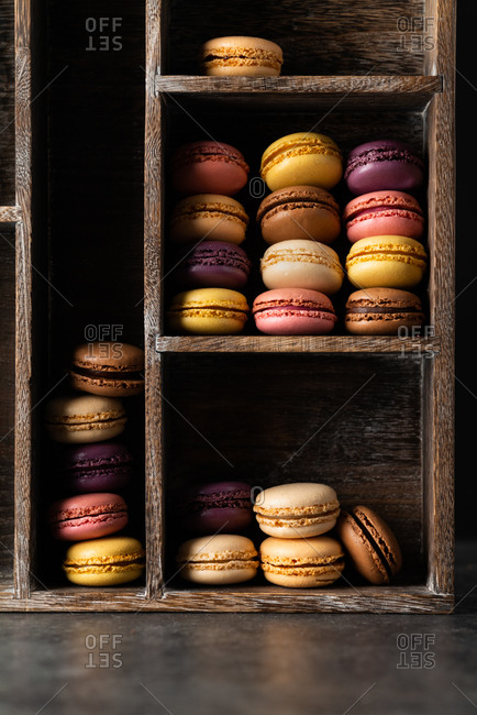 Macarons on a rustic wooden shelf in window light setting