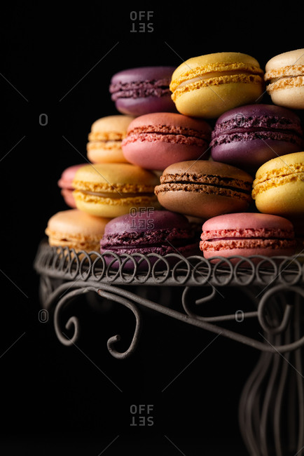 Macarons on a fancy wire stand on black background