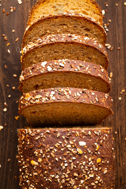 Sliced mulita grain bread loaf on wooden table