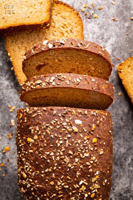 Sliced mulita grain bread loaf on gray surface