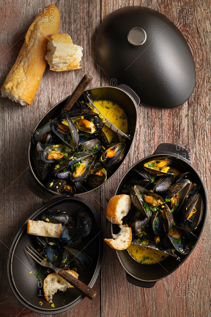 Mussels in cast iron mussel pots on wooden table