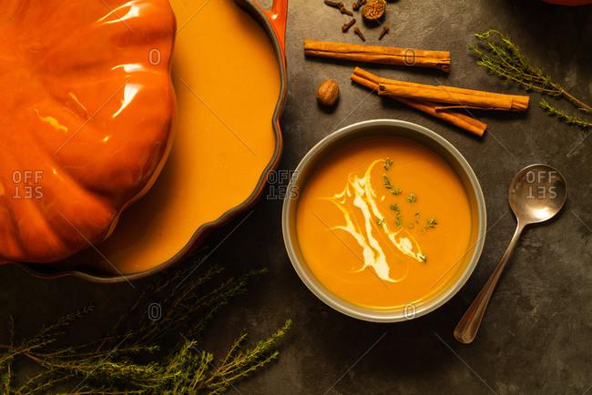 Pumpkin soup from cast iron pot on gray surface