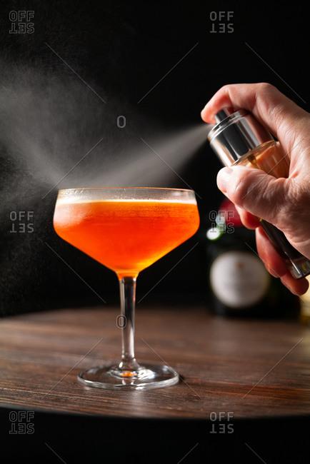 Bartender spritzing a custom cocktail