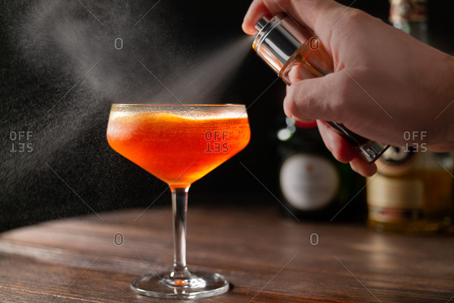Close up of a bartender spritzing a custom cocktail