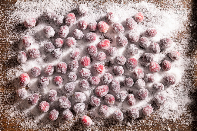 Sugar coated cranberries on wooden surface