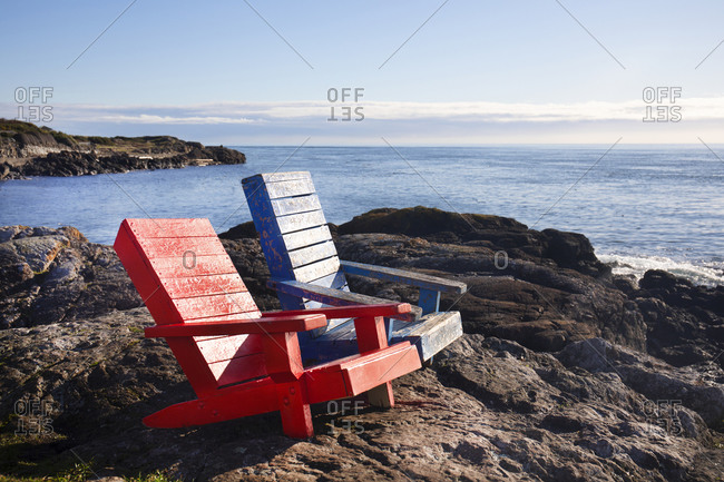 Two colorful lawn chairs looking out to sea, Victoria, British Columbia, Canada