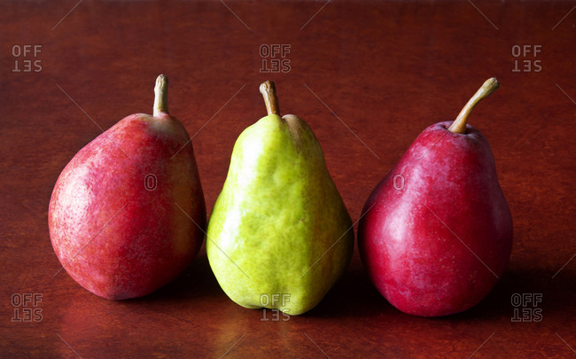 Three colorful pears on a counter top