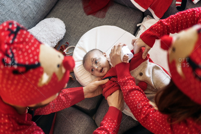 Unrecognized mother dressing her baby with Christmas clothes at home in Spain
