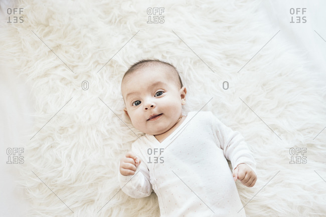 Lovely new born smiling and looking at camera while lying in a white blanket in Spain