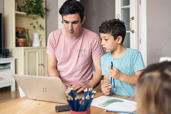 Cute boy having fun in the living room using laptop with his dad in Spain