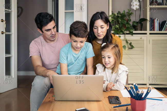 Lovely family having fun at home using laptop in Spain