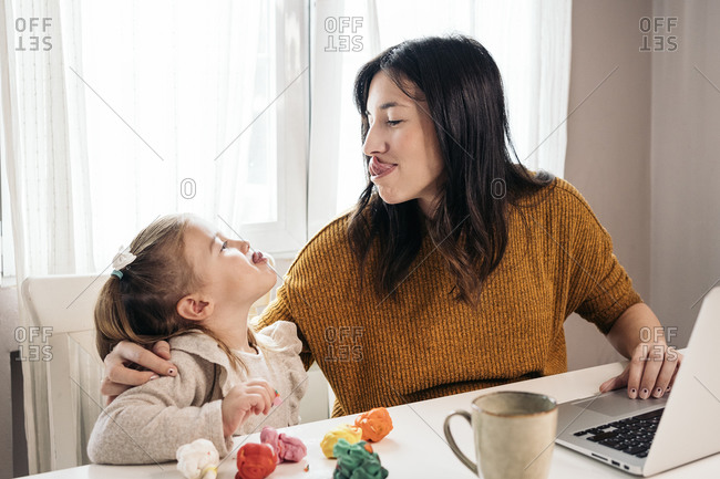 Lovely young girl doing funny faces at home with her mom in Spain
