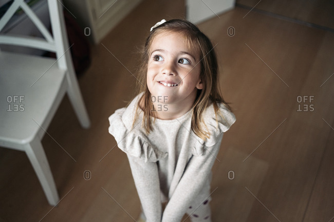 Cute little girl smiling and looking to the side in Spain