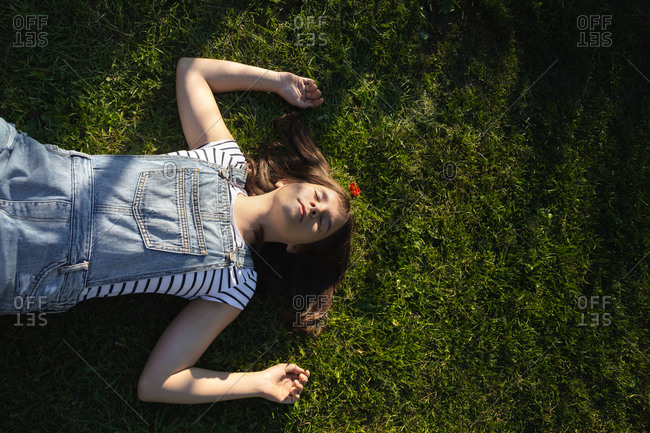 Teenage girl lies with her eyes closed on green grass on a summer day