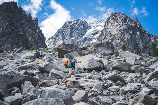 Climber walks up boulder at base of mountain in Washington