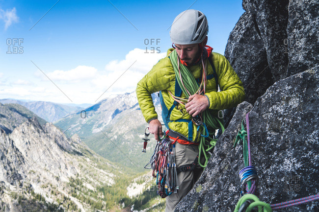 Man sorting through gear on harness while rock climbing in Washington
