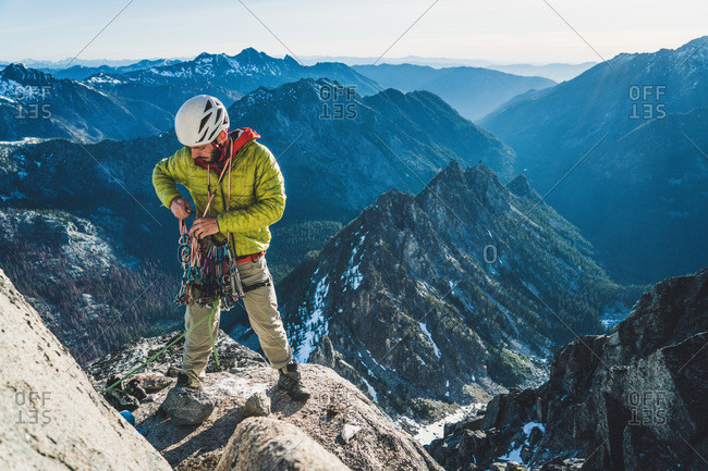 Man sorting climbing gear on alpine rock climb in Washington