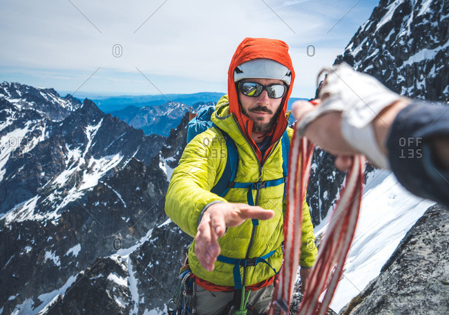 Man being handed gear during snowy alpine rock climb
