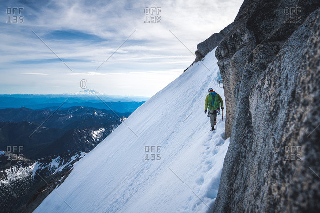 Man climber traversing steep snow field with Mt. Rainier in background