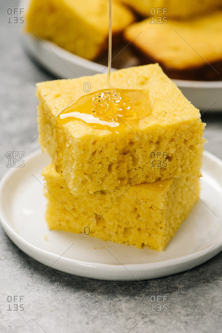 Drizzling honey over a short stack of cornbread