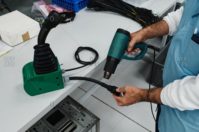 Man with hot air gun repairing a key of a remote control