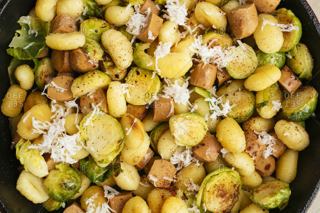 Gnocchi with brussels sprouts and vegan hot dog pieces in a pan