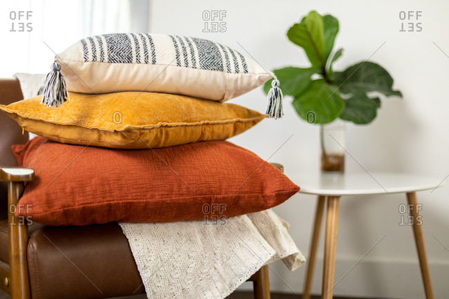 Stacked colorful fall pillows on chair