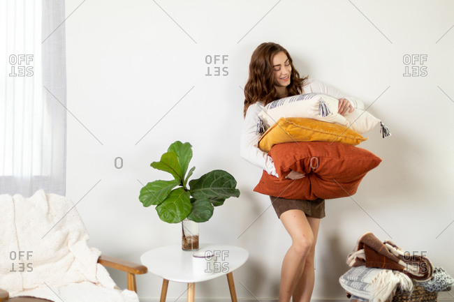 Woman holding stack of fall pillows