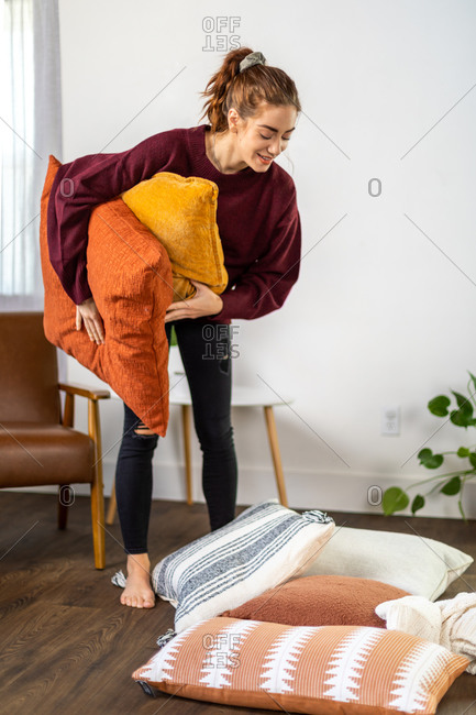Woman smiles while picking up pillows