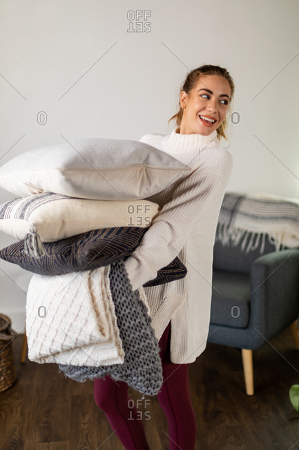 Woman holds blanket and pillows