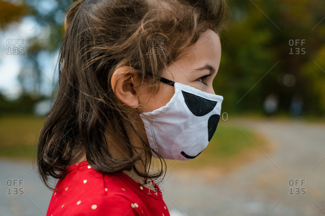 Preschool age girl wearing protective face mask outside in fall