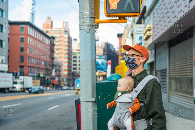 Father in face mask carrying baby girl while standing on sidewalk in city during covid-19 outbreak