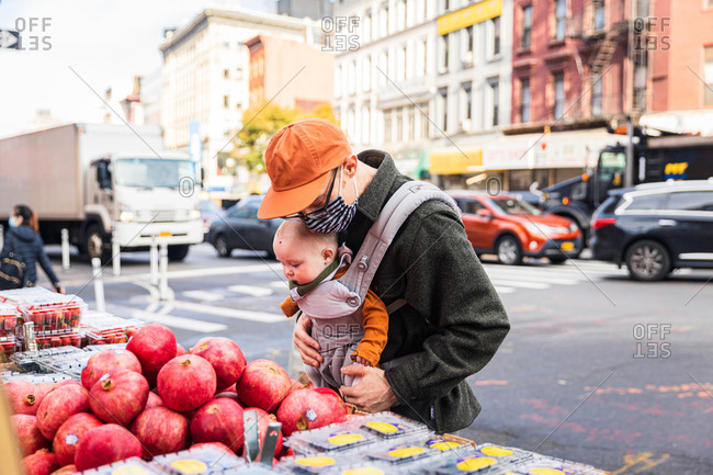 Father with baby girl buying pomegranates on street in city during coronavirus pandemic