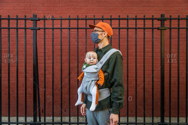 Father wearing face mask carrying cute daughter in baby carrier while standing by fence during coronavirus crisis