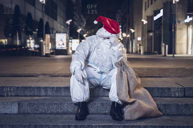 Desperate beggar dressed in the coverall used against the coronavirus, the mask, and the beard and hat of Santa Claus, sitting in the stairs in an empty square.