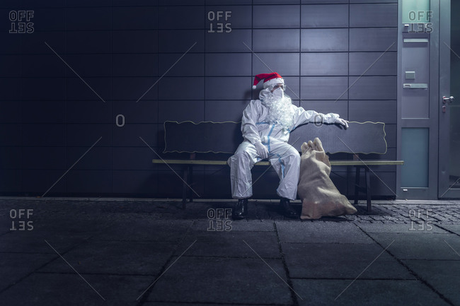 Volunteer dressed in the coverall used against the coronavirus, the mask, and the beard and hat of Santa Claus, sitting on a bench, tired, next to a hospital.