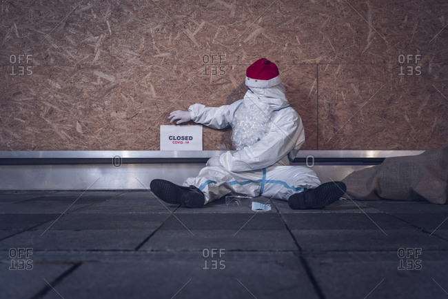 Man dressed as Santa Claus, but with a coverall, mask and glasses, used to protect himself from the coronavirus, sitting on the floor, in front of his closed store.